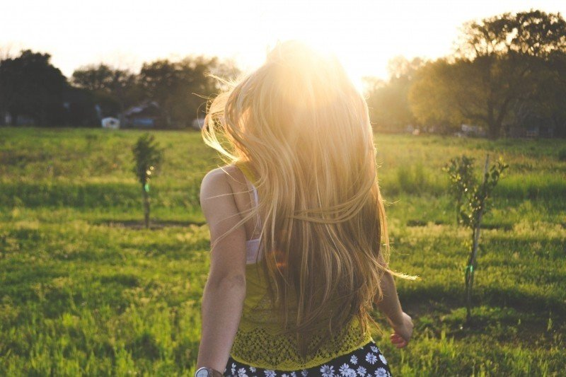 rear-view-of-blonde-woman-in-meadow-at-sunset.jpg